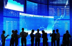 Stock traders standing in front of blue screens with stock data